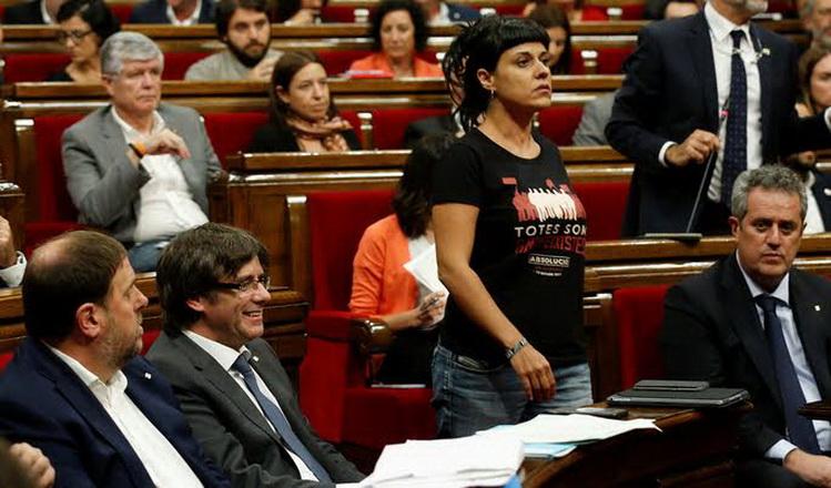 Leftist CUP party member Anna Gabriel walks past Catalonia's regional President Carles Puigdemont during a debate in the Catalonian regional Parliament in Barcelona, Spain, September 6, 2017. REUTERS/Albert Gea