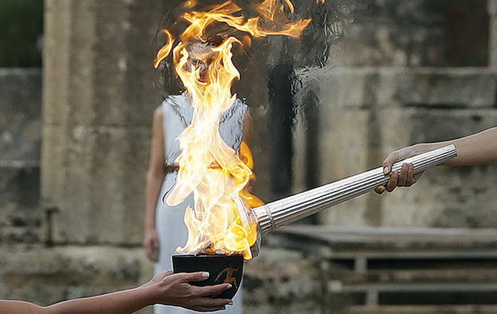 Actress Katerina Lehou, right, as high priestess, lights the torch during the lighting ceremony of the Olympic flame in Ancient Olympia, southwestern Greece, on Tuesday, Oct. 24, 2017. The flame will be transported by torch relay to Pyeongchang, South Korea, which will host the Feb. 9-25, 2018 Winter Olympics. (AP Photo/Thanassis Stavrakis)