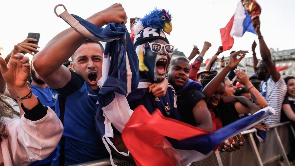 People celebrate France's first goal as they gather at a fan zone in Paris on July 10, 2018 to watch the Russia 2018 World Cup semi-final football match between France and Belgium. / AFP PHOTO / Eric FEFERBERG