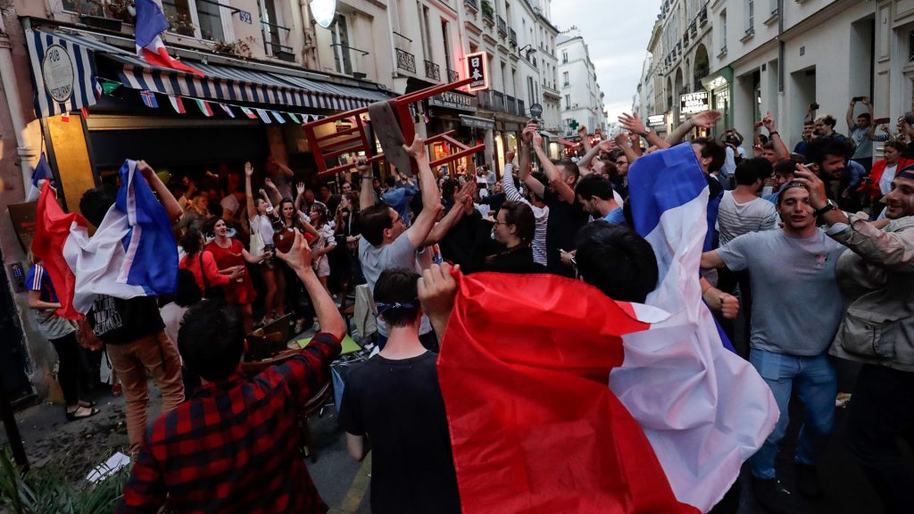 People celebrate France's victory outside a cafe in central Paris on July 10, 2018 at the final whistle at the Russia 2018 World Cup semi-final football match between France and Belgium. / AFP PHOTO / Thomas SAMSON